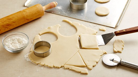 On floured surface, roll dough to 1/4-inch thickness. Cut with floured 2 1/2- to 3 1/2-inch shape cookie cutters (round, square, triangle). On ungreased cookie sheets, place cutouts 2 inches apart. Reroll dough and cut additional cookies.
